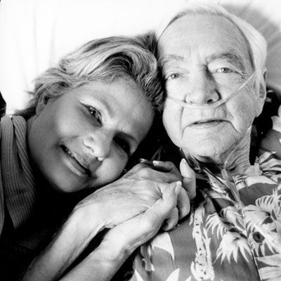 woman lying with father in hospital bed